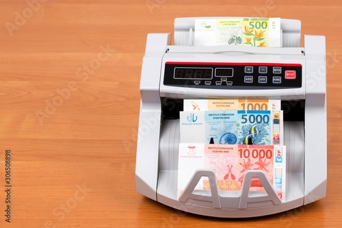 Fototapeta  French Pacific Territories money - Franc in a counting machine