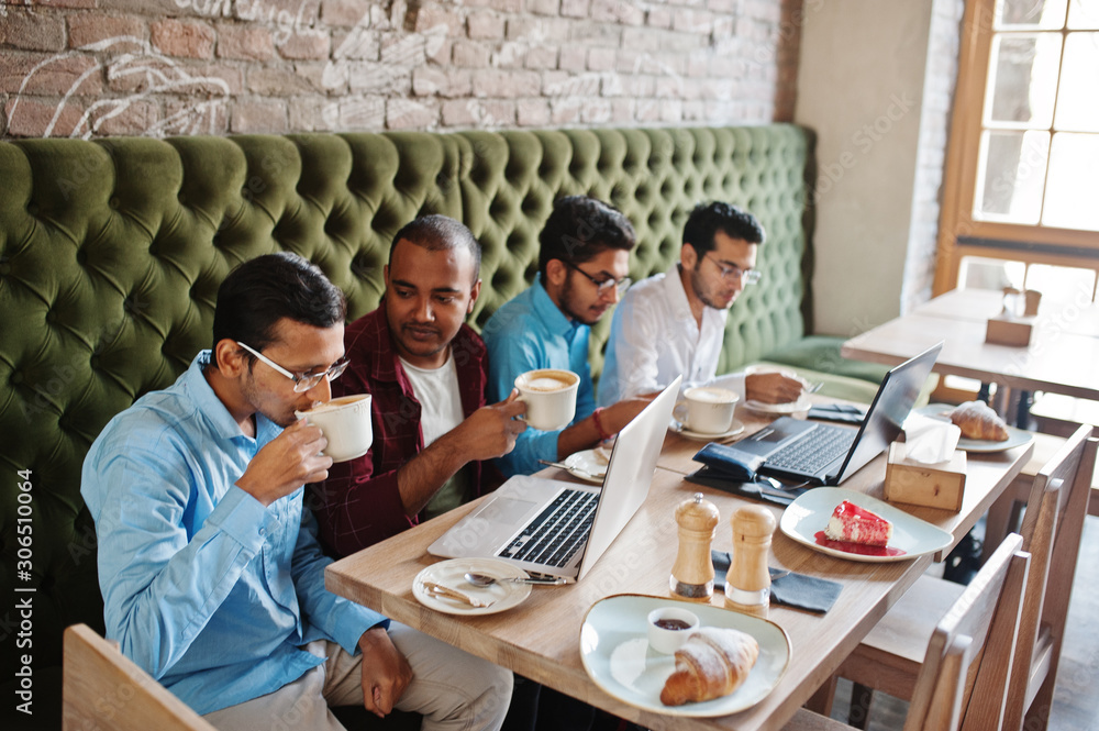 Fototapeta Group of four south asian men's posed at business meeting in cafe. Indians work with laptops together using various gadgets, having conversation and drink coffee.
