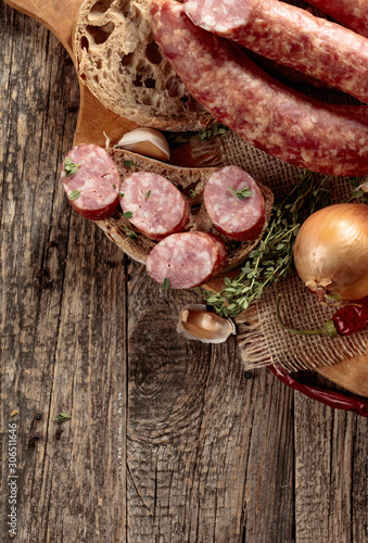 Fototapeta  Dry-cured sausage with bread and spices on a old wooden table.