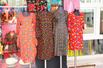 multi-colored women's dresses with a pattern of flowers on mannequin