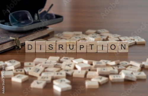 Fotografie, Obraz  disruption the word or concept represented by wooden letter tiles