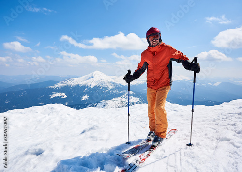 Fotomural Smiling sportsman skier in helmet and goggles standing on skis holding ski poles in deep white snow on copy space background of bright blue sky and highland landscape
