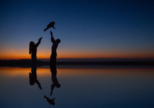 Happy Child And Parents Walk At Sunset. Dad Hugs Daughter And Whirls In Flight. Silhouette Of A Family Walking In The Sun. Mom Dad And Baby. The Concept Of A Happy Family. Family Lifestyle.