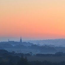 Foggy Morning Sunrise In Brittany, France. Blue Hills Covered With Forest.