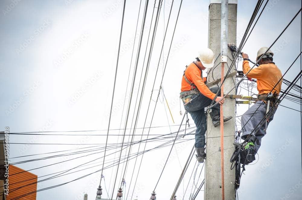 Fototapeta Electricians are climbing on electric poles to install and repair power lines.