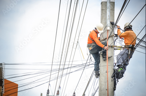 Fototapeta Electricians are climbing on electric poles to install and repair power lines. obraz