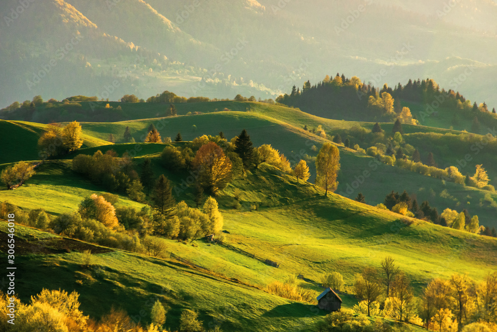 Fototapeta mountainous countryside at sunset. landscape with grassy rural fields and trees on hills rolling in to the distance in evening light. distant ridge and valley in haze. fantastic scenery in springtime