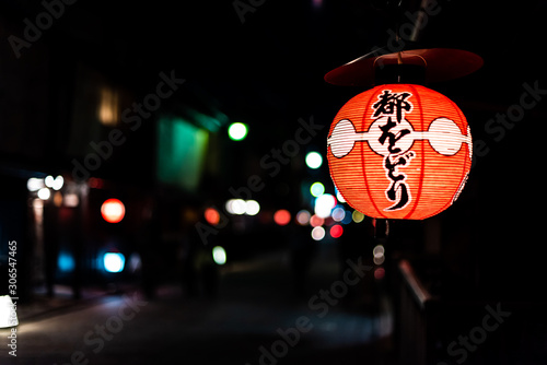 Kyoto, Japan - April 16, 2019: Narrow alley street in Gion district at night with closeup of illuminated red paper lanterns and black bokeh backgroud