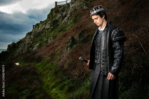 Obraz na plátně Handsome king with sword stands in contemplation with hill and parts of keep in