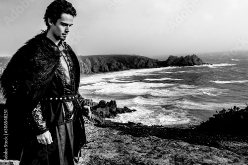 Knight with leather costume, fur cloak and sword standing in contemplation on cliff top with ocean in background Wallpaper Mural
