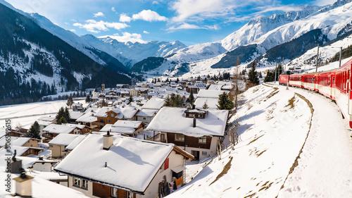 Photo Train rouge du glacier express traverse un paysage enneigé au dessus d'un villag
