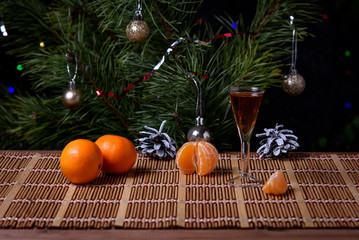 A glass of cognac with tangerines on the surface of the table against the background of the Christmas tree.