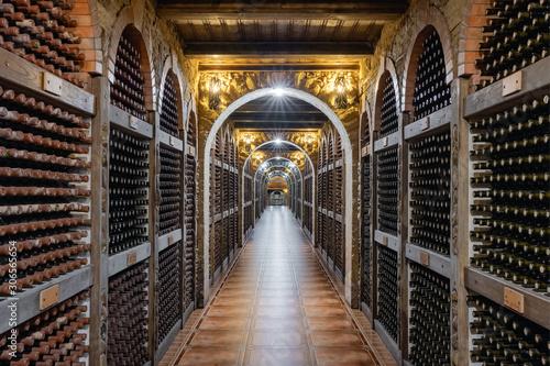Wine bottles stacked up in underground wine cellar Wallpaper Mural