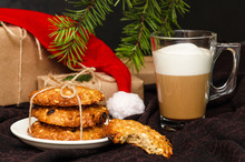 Christmas Oatmeal Cookies, Transparent Mug Of Coffee With Milk Or Cappuccino, Gift Boxes In Kraft Paper, Hat Forgotten By Santa Claus On Brown Background. One Cookie Is Bitten Off. Holidays Concept