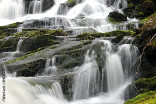 cascading waterfall of Smooth flowing water with green moss on rocks