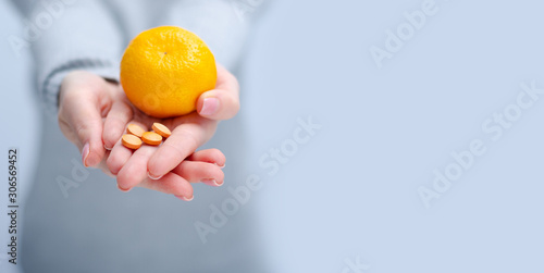 Stampa su Tela Woman holding tangerine and vitamin C, medecine, health care on gray light backg