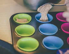 Hand Pouring Vegan Cupcake Batter Into Colourful Shapes
