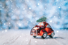 Little Red Toy Car Carries A Christmas Tree On A Blue Blurred Background