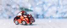 Close-up Of A Small Toy Car Carries A Xmas Tree On The Roof, Concept Christmas And New Year