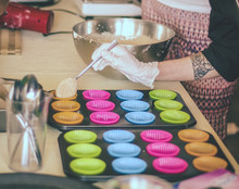 Hand With Tattooed Skin Pouring Vegan Cupcake Batter Into Colourful Shaoes