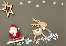 Christmas Flat Lay With Natural Decoration  Wooden Christmas Tree Toys Deer Pulling Sleigh With Santa,  And White Snowflakes On Brown Backgound