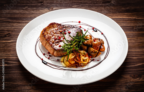 Fotografering Grilled sirloin steak and vegetables on wooden background