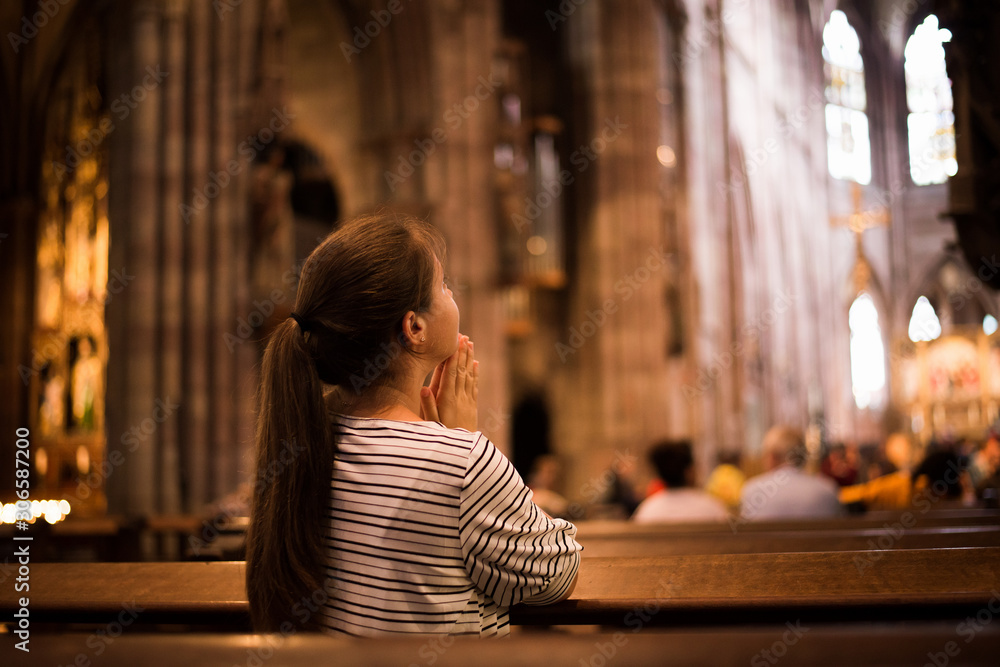Fototapeta Young girl praying in church standing on her knees