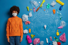 Ethnic Curly Woman Wears Protective Face Mask, Dressed In Knitted Orange Jumper And Denim Pants, Looks Unhappily, Being Disturbed By Air Pollution And Serious Problem Of Contamination, Plastic