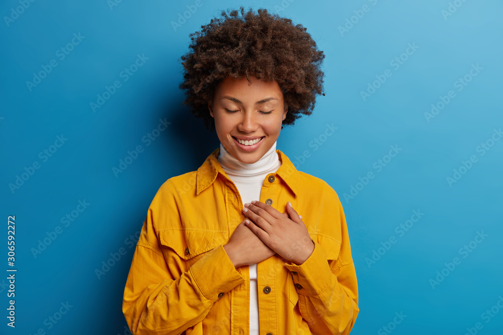 Fototapeta Tender feminine woman keeps hands on heart, has grateful look, appreciates effort, has eyes closed, wears yellow shirt, isolated over blue background, receives touching compliment, smiles pleasantly