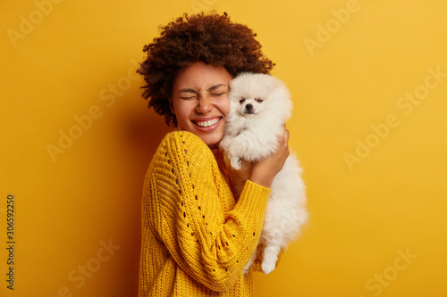 Fotomural  Pleased happy Afro girl gets lovely puppy, plays and embraces four legged friend with love, stands against yellow background, wears knitted jumper