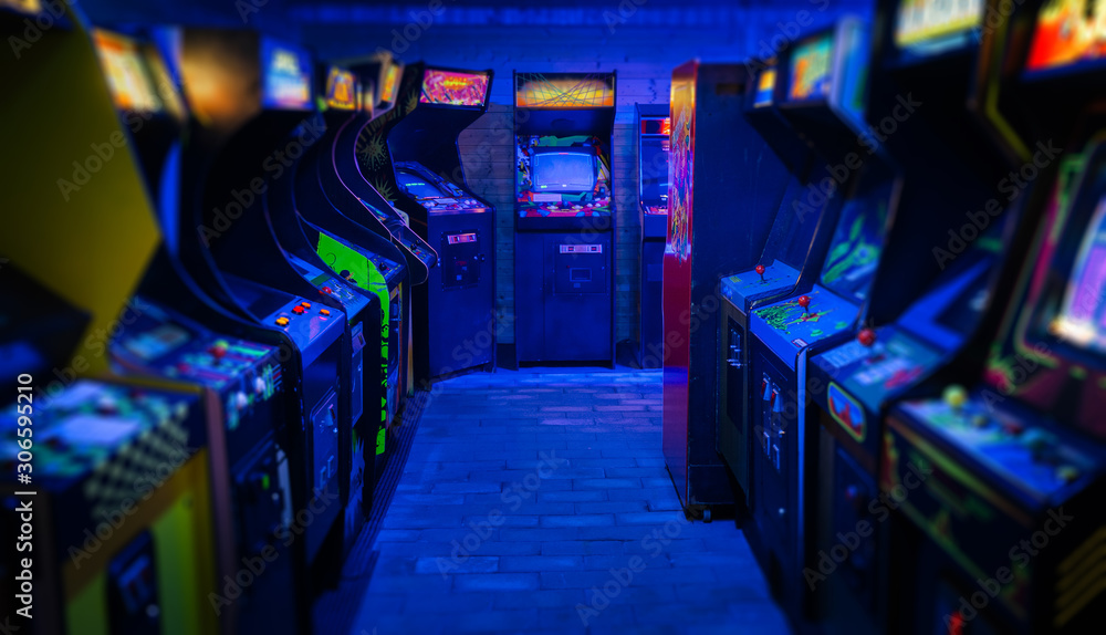 Old Vintage Arcade Video Games in an empty dark gaming room with blue light with glowing displays and beautiful retro design