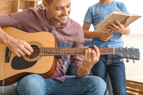 Fotomural  Father and his little son with guitar at home