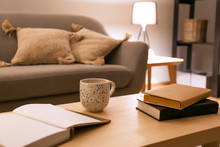Books With Cup Of Coffee On Table In Room At Night