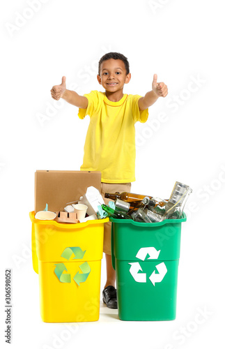 Fototapety, obrazy: Little African-American boy showing thumb-up near containers with trash on white background. Concept of recycling