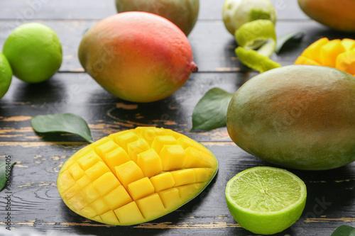 Cuadros en Lienzo Sweet ripe mangoes and limes on dark wooden background