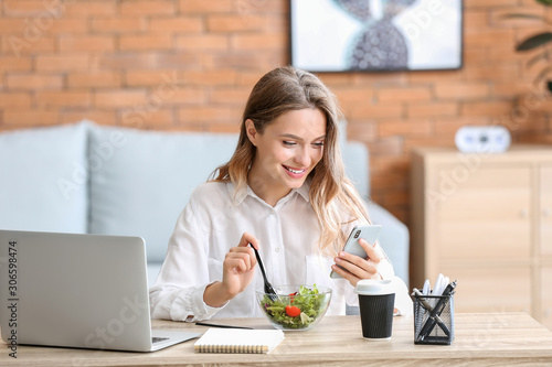 Fotografia Woman eating healthy vegetable salad in office