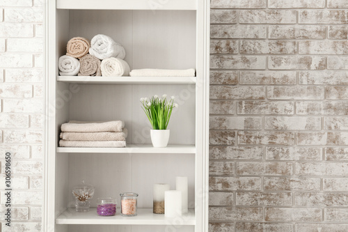Shelf unit with towels and cosmetics near brick wall in bathroom Fototapet