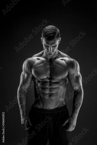 obraz PCV Very brawny guy bodybuilder posing. Beautiful sporty guy male power. Fitness muscled man in studio. Dark background.