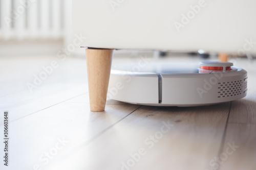 Valokuva  Robot vacuum cleaner vacuuming under the bed