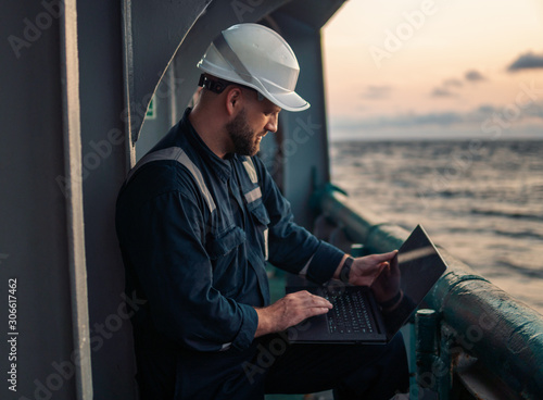 Fotomural Marine chief officer or captain on deck of vessel or ship watching laptop