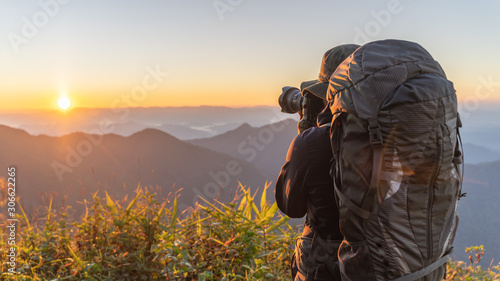 Photo A man traveler with a backpack stands on a hill of beautiful mountain landscape