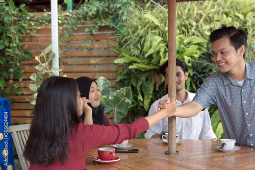 Платно Happy multiracial asian young people hang out outdoors together give high five g