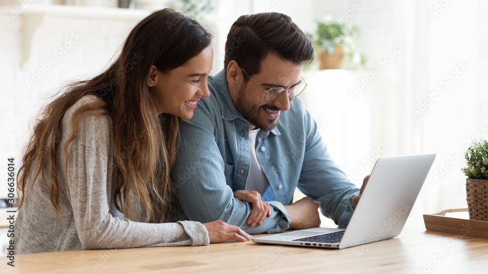 Fototapeta Happy young couple bonding laughing using laptop sit at table