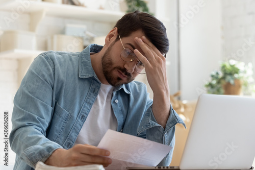 Fotografía Upset frustrated young man holding reading postal mail letter