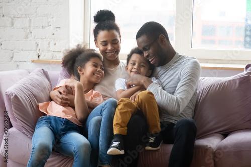 Obraz Happy biracial family with kids relax on cozy sofa - fototapety do salonu