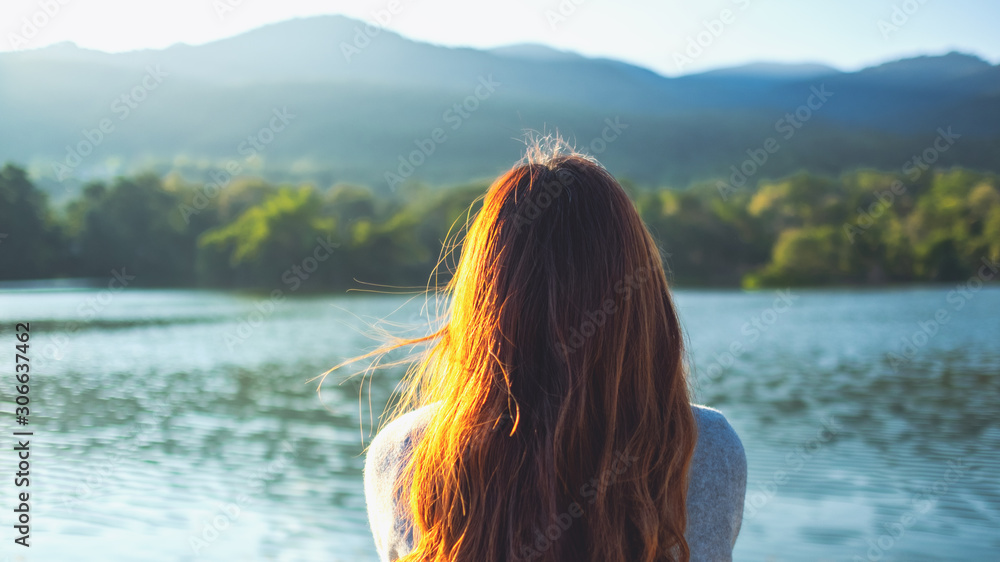 Fototapeta A woman sitting alone by the lake looking at the mountains with green nature background