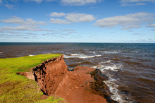 Erosion Red Rocks Falling Into The Ocean On Pei Island