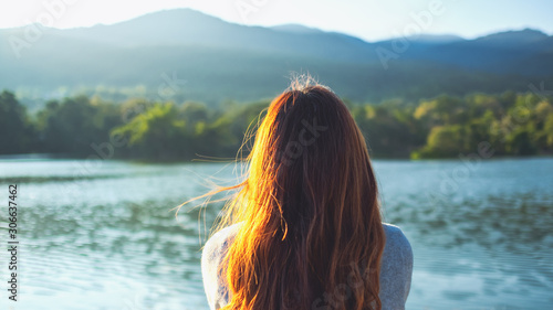 Obraz na plátně A woman sitting alone by the lake looking at the mountains with green nature bac