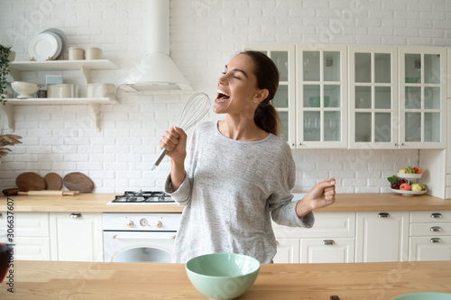Obraz Happy woman singing in beater microphone dancing cooking in kitchen - fototapety do salonu