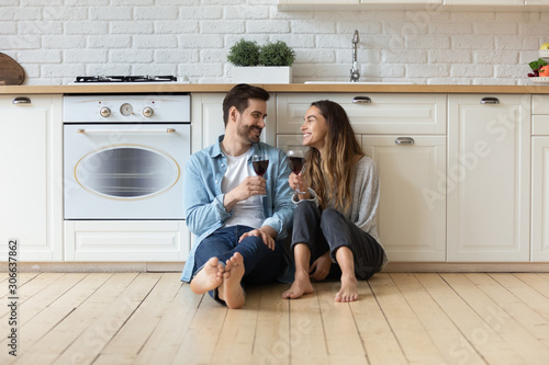 Happy affectionate couple talking drinking wine sit on kitchen floor Canvas Print